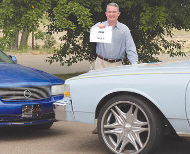 Robin Carroll holds a for sale sign as he stands behind one of the cars to be auctioned